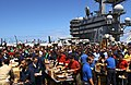US Navy 060628-N-7526R-055 Sailors swarm food tables on the flight deck of USS Ronald Reagan (CVN 76) during a steel beach picnic.jpg