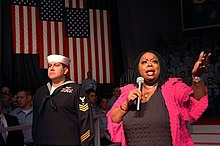 US Navy 070221-N-7883G-020 Singer and performer Carol Woods sings to service members in the hangar bay aboard USS Kitty Hawk (CV 63) prior to the visit by Vice President Dick Cheney.jpg