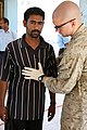 US Navy 070609-M-6412C-018 A Navy corpsman with the Fallujah Police Transition Team, Regimental Combat Team 6, checks a potential Iraqi Police recruit for medical problems during the application process.jpg
