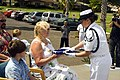 US Navy 070717-N-6674H-093 Master-at-Arms 2nd Class Illianna Thomas of Naval Station Pearl Harbor's Honor Guard presents Jeanne Haack-Marcuci, daughter of Pearl Harbor survivor Chief Gunner's Mate Raymond Haack.jpg