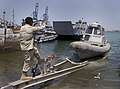 US Navy 090929-N-6725B-006 Master at Arms 1st Class Pedro Rocha, a member of the harbor patrol unit at Camp Lemonnier, Djibouti (CLDJ), guides an eight meter harbor patrol boat.jpg