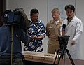 US Navy 101109-N-2198T-010 A film crew from Hawaii News Now records Lt. Bryan Heintschel, center, assigned to Navy Environmental and Preventive Med.jpg