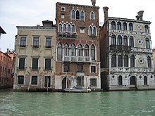A row of three waterside Venetian buildings, having between three and five stories, with contrasting arrangements of arcades, windows and balconies.