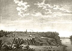 A black-and-white drawing of a fort and various small buildings on a bluff surrounded by trees above a river