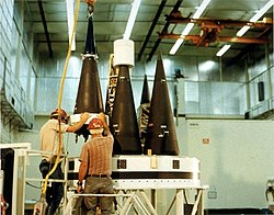 Technicians secure a number of Mk-21 re-entry vehicles on a Peacekeeper MIRV bus.