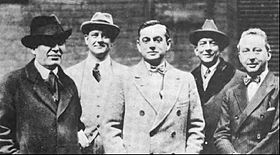 black and white photograph of five well-dressed men standing facing the camera