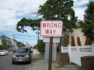"A reverse-colors ""Wrong Way"" sign on..."