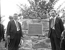 two men standing by a stone pillar with a bronze historical marker for the York Imperial apple