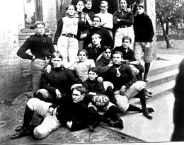 Football team photo outside a building; some players are standing, and others are sitting on the steps.