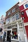 foto van Tweezijdig aangebouwd winkelpand, gevel in overgangsarchitectuur met een winkelpui in een mengeling van eclectische en Jugendstil vormen