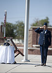 A tilted chair symbolizes a POW-MIA Service member as U.S. Air Force Airman 1st Class Tayna Flores, with the 49th Materiel Maintenance Support Squadron, renders a salute during the POW-MIA recognition ceremony 120921-F-FJ989-070.jpg