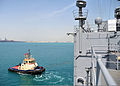 A tugboat assists the amphibious dock landing ship USS Rushmore (LSD 47) as the ship departs Manama, Bahrain, March 28, 2013, following a scheduled port visit 130328-N-YQ852-056.jpg