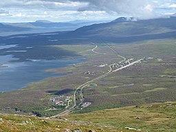 Abisko, set fra bjerget Nuolja.   I forgrunden ses Abisko turiststation og den nedre del af Abiskocanyonen skimtes, længre bort Abisko Östra.   Til venstre i billede ses Torneträsk.