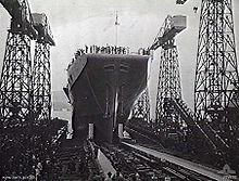 Photograph of the bow of an aircraft carrier as it slides backwards down a slipway. Crowds are gathered around the slipway, underneath several cranes