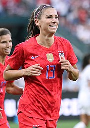 Footballer Alex Morgan, pictured jogging in a red U.S. uniform with the number 13.