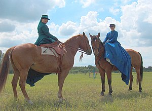 Two ladies riding sidesaddles.