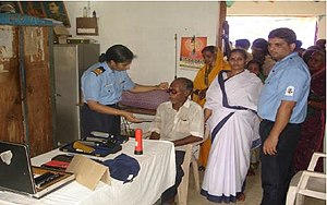 Healthcare in India - A medical provider from INHS Nivarini examining a patient in rural India, with other patients waiting in line behind