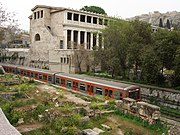 An ISAP train (Green Line) passes by the Stoa of Attalus in central Athens.