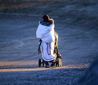 An Inuit woman uses a traditional amauti and a modern western stroller Baby Carriage 2002-08-02.jpg