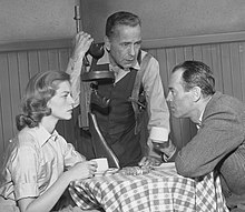 Lauren Bacall in black and white sitting at a table with Humphrey Bogart and Henry Fonda while performing a scene on an episode of The Petrified Forest in 1956