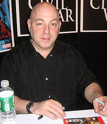 Man with shaved head sits at a table, a botte of water beside him. He holds a pen, and is looking into the camera.