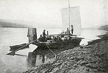 Prospectors sailing toward Dawson in boat on upper Yukon River, 1898