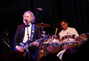 Mickey Hart - Mickey Hart (in background, playing drums) and Bob Weir (playing guitar) performing at the Mid-Atlantic Inaugural Ball during the presidential inauguration of Barack Obama, January 20, 2009