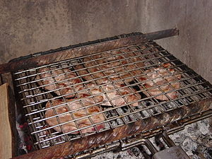 Regional variations of barbecue - Boerewors and pork in a concrete braai structure