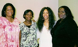 Badu alongside Brenda Cherry, Creola and Shaquanda Cotton at the Africa Care Academy 10th Annual Educational Awards Banquet in Dallas, Texas. Brenda, Shaquanda, Erykah, and Creola.jpg