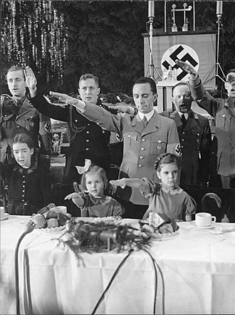 Goebbels children - Joseph Goebbels with his daughters, Hilde (center) and Helga (right), at a Christmas celebration in the Saalbau (Hall) Friedrichshain, Berlin, 1937, during the singing of the national anthems.
