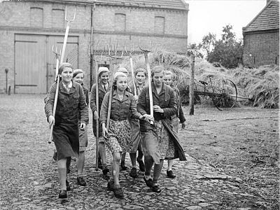 "Teenage girls in agricultural work in the occupied territories, one of the possible duties assigned by the Bund Deutscher Madel (League of Young German Women), the female version of the Hitler Youth, with compulsory membership for girls. The caption in Das Deutsche Madel, in its May 1942 issue, states: ""bringing all the enthusiasm and life force of their youth, our young daughters of the Work Service make their contribution in the German territories regained in the East"". Bundesarchiv Bild 183-E10868, BDM in der Landwirtschaft.jpg"