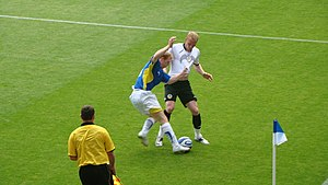 Jérémy Mathieu - Mathieu challenging Chris Burke for the ball in a 2009 friendly at Cardiff City