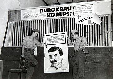 COLLECTIE TROPENMUSEUM Militairen bij een affiche met het portret van Stalin door hen aangetroffen op het kantoor van de Pemuda Sosialis Indonesia (Pesindo) TMnr 60054585.jpg