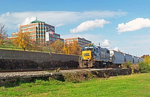 "A blue diesel locomotive, with ""CSX"" in blue letters on its yellow front, pulling several hopper cars along a railroad track. In the background are some postmodernist brick office buildings with green spired roofs."