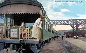 Carolina Special - A colorized postcard view of an open-deck observation car with drumhead at the end of a Carolina Special consist at Asheville, North Carolina, the female passengers' garb dating it prior to World War I, in the train's first decade of operation.