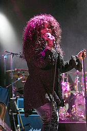 A woman is performing on stage. She wears a dark sweater and metallic-colored jeans.