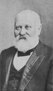portrait shot of a man in late middle age with white hair and beard. He is seen to wear a suit with vest and a small bow-style tie.