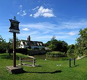 The village green in Comberton in Cambridgeshire, UK, with a pond, a village sign and a bench to enjoy the view