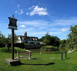 Village green - A village green in Cambridgeshire, England. Benches face a large pond - a common sight in many village greens.