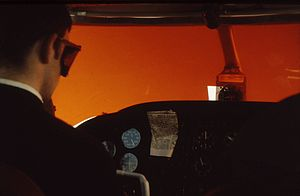 Sensory illusions in aviation - Blind flying. The pilot wears goggles blocking the colors transparent through the orange plastic sheet in front of him. The instructor wearing no goggles has an outside view tinted orange.