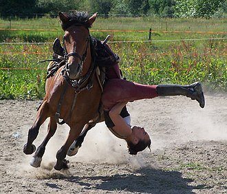 Trick riding - The Cossack Drag or Death Drag.