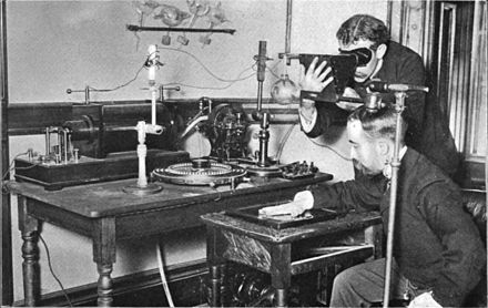 Taking an X-ray image with early Crookes tube apparatus, late 1800s. The Crookes tube is visible in center. The standing man is viewing his hand with a fluoroscope screen. The seated man is taking a radiograph of his hand by placing it on a photographic plate. No precautions against radiation exposure are taken; its hazards were not known at the time. Crookes tube xray experiment.jpg