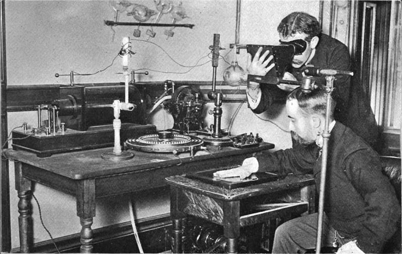 Taking an X-ray image with early Crookes tube apparatus in 1896. The Crookes tube is visible in the centre. The standing man is viewing his hand with a fluoroscope screen. This was a shortcut method for setting up the tube.No precautions against radiation exposure are being taken. Crookes tube xray experiment.jpg
