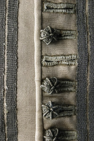 Ribbed thread-wrapped buttons in buttonholes reinforced with woven trim.
