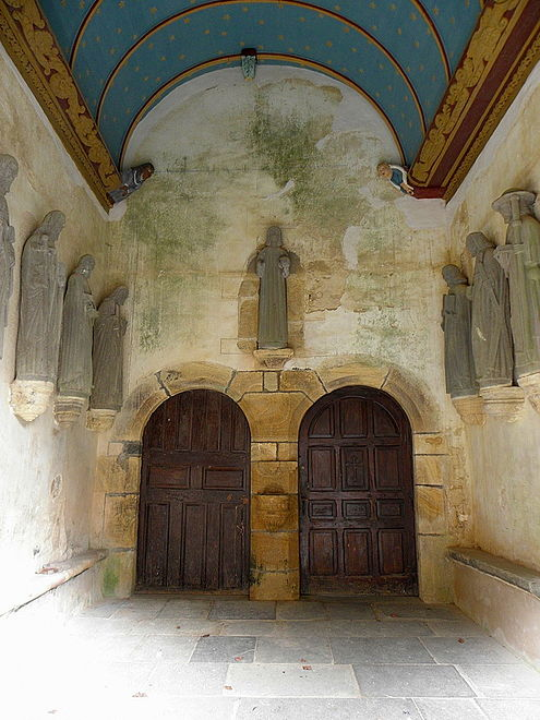 Inside the south porch with a view of the two doors accessing the church. Note the carved sablières at the top of the wall and above the statues of the apostles.