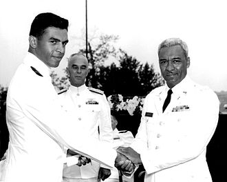 Black cadets at the United States Coast Guard Academy - Ensign Merle J. Smith, Jr. (left) is congratulated by his father, Colonel Merle J. Smith, Sr., AUS (right) upon his graduation from the Coast Guard Academy in 1966.  Admiral Willard J. Smith, Commandant, is in background.  Ensign Smith was the first African-American graduate of the U.S. Coast Guard Academy.