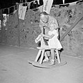 Een blond meisje op een hobbelpaard met man (haar vader), Bestanddeelnr 255-6898.jpg