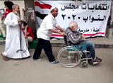 Elderly Egyptian voters in front of a polling station; to cast their votes in the 2020 elections for the Egyptian Parliament