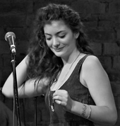 A black-and-white photo of Lorde performing. She is seen touching her hair and smiling while looking downwards