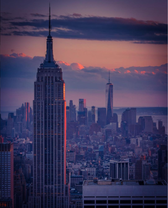 The Empire State Building in the foreground looking southward from the top of Rockefeller Center, with One World Trade Center in the background, at sunset. The Midtown South Community Council acts as a civic caretaker for much of the neighborhood between the skyscrapers of Midtown and Lower Manhattan. Past Vs. Present.png